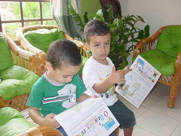 Crianças lendo O Brasileirinho, primeiro jornal do Brasil feito com a participação de crianças e jovens